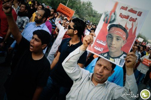Jawad Al-Sheikh carrying his killed son's photo in a peaceful demonstration