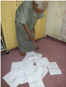 Ashour Hassan Ali pointing at all the summons they received for his sons
